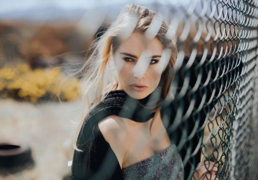 grillage-femme-blonde-portrait-vent