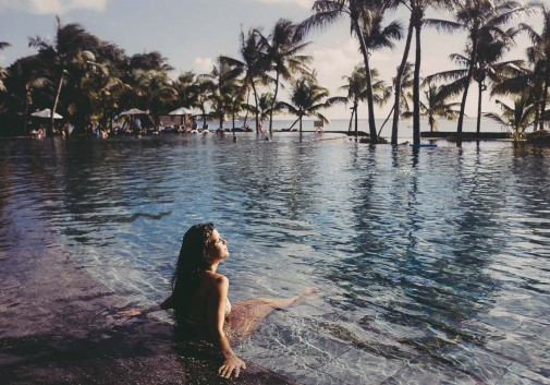 femme-brune-piscine-palmier-sexy