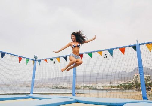 femme-saut-trempoline-joie-brune
